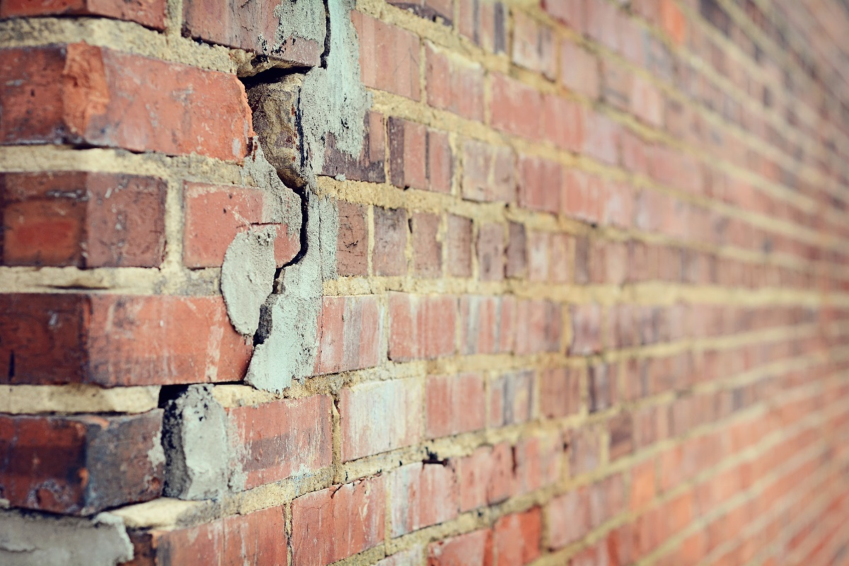 A wall of a house with bricks that have cracks in them